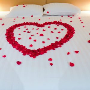 Wedding bed topped with rose petals, Thai style wedding